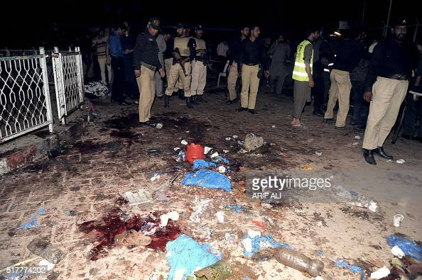Pakistani emergency workers and police officers gather at a bomb blast site in Lahore on March 27 2016 At least 56 people were killed and more than...
