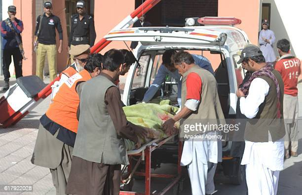 Pakistani emergency workers carry a victim in Quetta Quetta on October 25 after militants attacked the training college At least 61 cadets and guards...