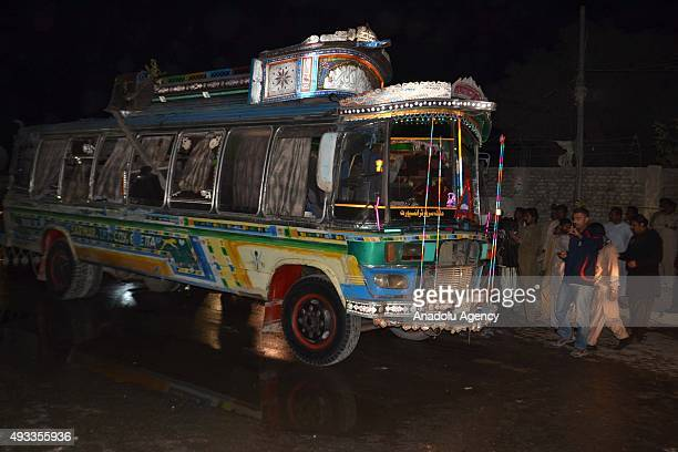 Pakistani emergency workers security forces and local people gather around a passenger bus hit by bomb blast in Quetta Pakistan on October 19 2015 At...