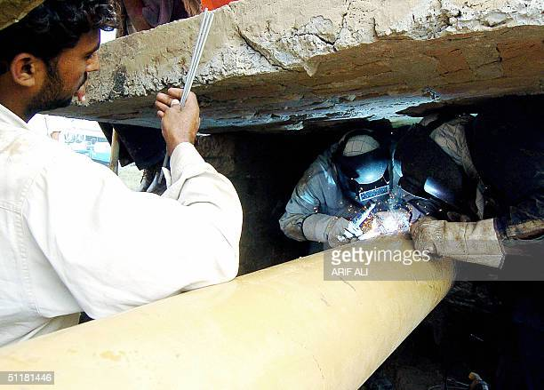 Pakistani engineers repair a gas pipeline which was damaged by a bomb blast late 16 August 30 kms north of Lahore 17 August 2004 The pipeline blast...