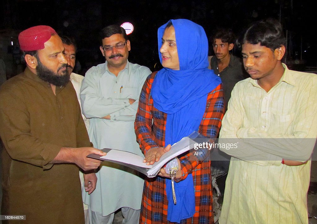 Pakistani eunuch Sanam Fakir (C), 32, shows documents as he talks to his election campaign staff ahead of general elections in Sukkur, about 800 kilometres (500 miles) southwest of Islamabad, on February 25, 2013. A member of Pakistan's transgender community is to contest upcoming general elections on a ticket of equal rights, saying the community has more to offer than begging or dancing at weddings. AFP PHOTO/Shahid ALI