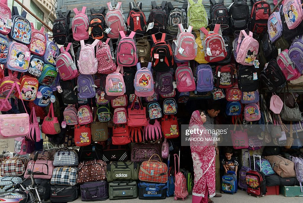 A Pakistani family chooses a school bag at a shop in Rawalpindi on April 15, 2014. Pakistan has re-entered the international bond market after a seven-year gap, the finance ministry said Wednesday, raising $2 billion to boost dwindling foreign exchange reserves and shore up the rupee. AFP PHOTO/Farooq NAEEM