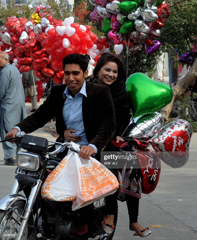 A Pakistani family holds heart shaped balloons purchased from a road-side vendor on Valentine's Day in Lahore on February 14, 2013. Pakistan's media regulator Wednesday asked television and radio stations to avoid offending religious sentiments and corrupting the nation's youth in their Valentine's Day broadcasts. AFP PHOTO/Arif ALI