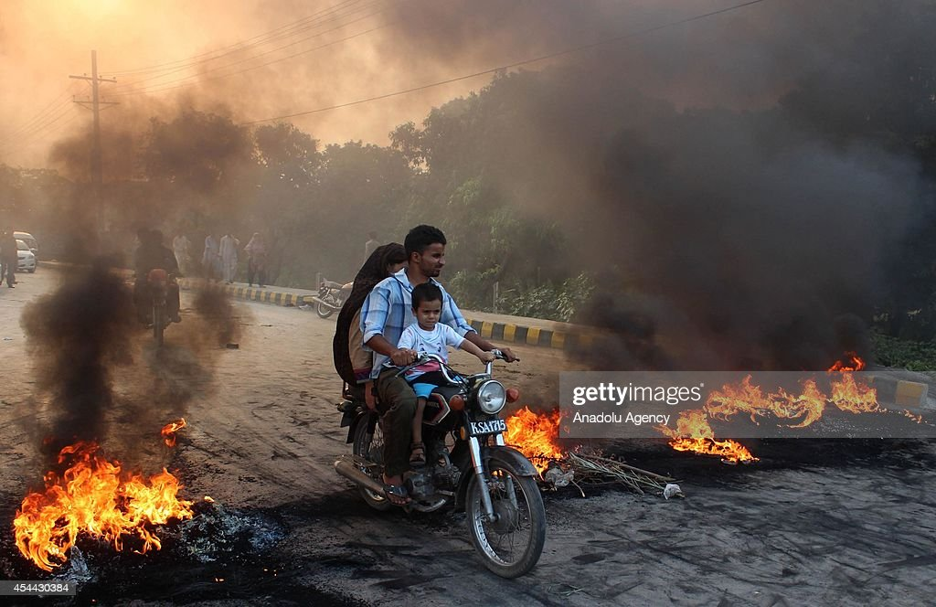 A Pakistani family ride on bike as Supporters of the Pakistan Tehreek-e-Insaf (PTI) political party block the road with burning tires in Lahore, Pakistan on August 31, 2014. At least 4 people killed and more than 500 wounded in clashes between thousands of police and protesters in Pakistan's capital Islamabad Saturday, as a fortnight-long political impasse took a violent turn when opposition groups attempted to storm the prime minister's residence.