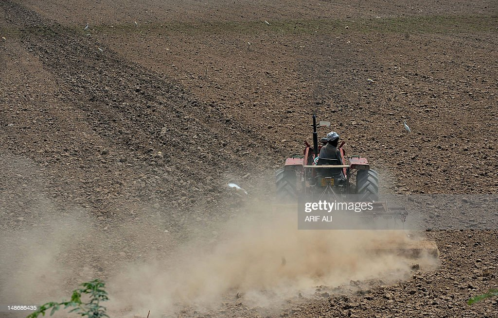 A Pakistani farmer ploughs field for rice plantation in Lahore on July 19, 2012. Around 68 percent of Pakistan's population depends on agriculture for their livelihood, with the agricultural sector contributing nearly a fourth of the country's GDP. AFP PHOTO/Arif ALI