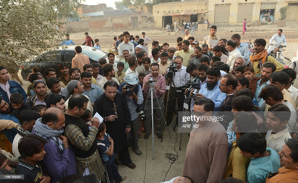 Pakistani farmers gather around media representatives following the execution of Ajmal Kasab, who was the sole surviving gunman of the 2008 Mumbai attacks, at Kasab's village in Farid kot, some 370 kilometres (230 miles) southeast of the Pakistani capital Islamabad on November 21, 2012. Farmers in the village of the Pakistani gunman executed Wednesday for the 2008 Mumbai massacre lashed out at India and hounded out journalists who asked about their notorious son. AFP PHOTO/Arif ALI