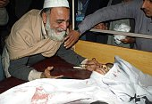 A Pakistani father mourns beside the body of his son at a hospital following an attack by Taliban gunmen on a school in Peshawar on December 16 2014...