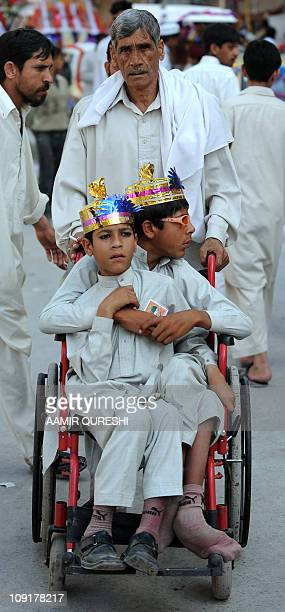 A Pakistani father pushes a wheelchair carrying his disabled sons at a religious procession during celebrations marking EideMiladunNabi the birth of...