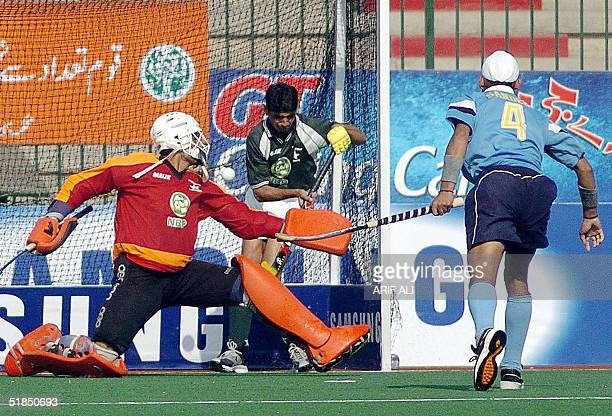 Pakistani field hockey goalkeeper Salman Akbar and Zeeshan Ashraf try to stop a ball hit by Indian player Sandeep Singh during their men's Champions...