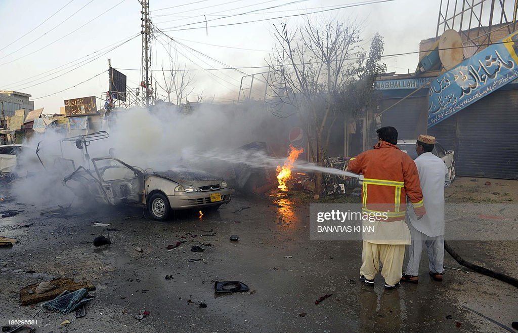 A Pakistani firefighter extinguishes a burning vechile after a bomb explosion in Quetta on October 30, 2013. A bomb exploded in a crowded car repair market in restive southwest Pakistan, killing at least five people and wounding 17 others, officials said. AFP PHOTO/Banaras KHAN