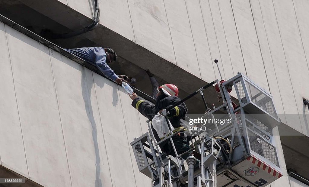 A Pakistani firefighter gives water to a man who was stuck in a burning building in Lahore on May 9, 2013. At least three persons fell from the 13-story LDA plaza situated on Lahore's Edgerton road 9 trying to avoid a fire that engulfed the building. AFP PHOTO/ Arif ALI