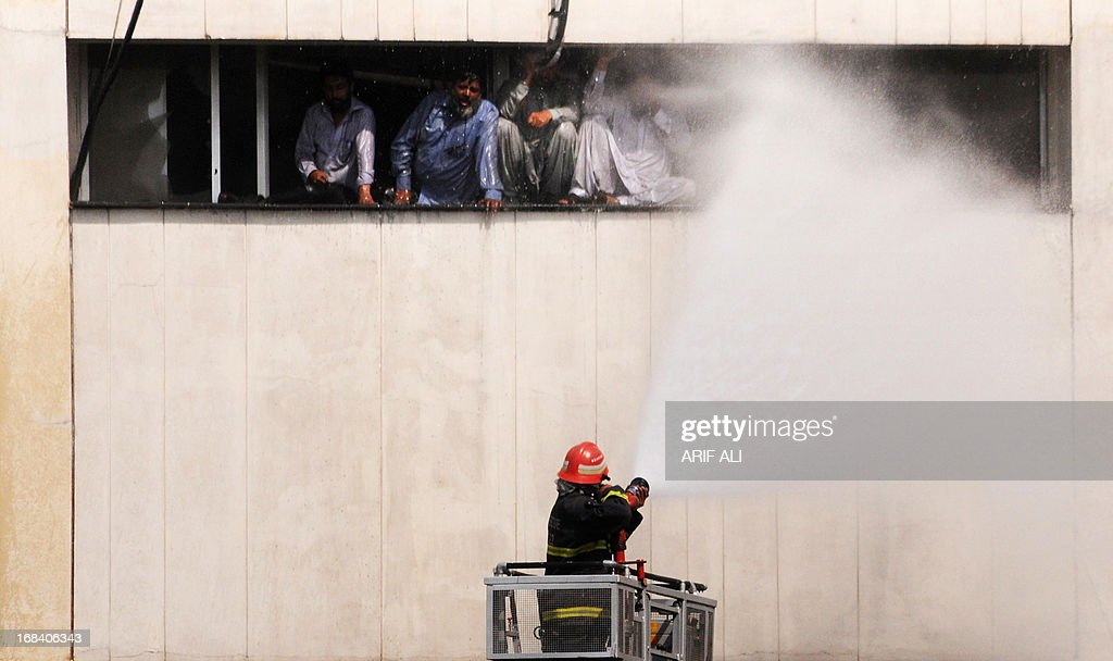 A Pakistani firefighter sprays people, trapped in a burning building, with water in Lahore on May 9, 2013. At least three persons fell from the 13-story LDA plaza situated on Lahore's Edgerton road 9 trying to avoid a fire that engulfed the building. AFP PHOTO/ Arif ALI