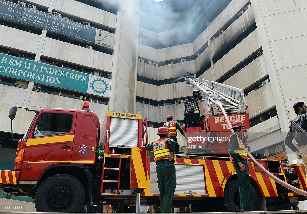 Pakistani firefighters extinguish fire at a high rise state-run building in Lahore on May 10, 2013. Around one dozen people were killed and scores were wounded in the fire which possibly erupted due an eletrical short circuit in two rooms on seventh floor on May 9. AFP PHOTO / ARIF ALI