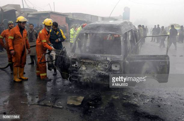 TOPSHOT Pakistani firefighters extinguish the wreckage of a vehicle after a suicide bomb attack on the outskirts of Peshawar on January 19 2016 At...