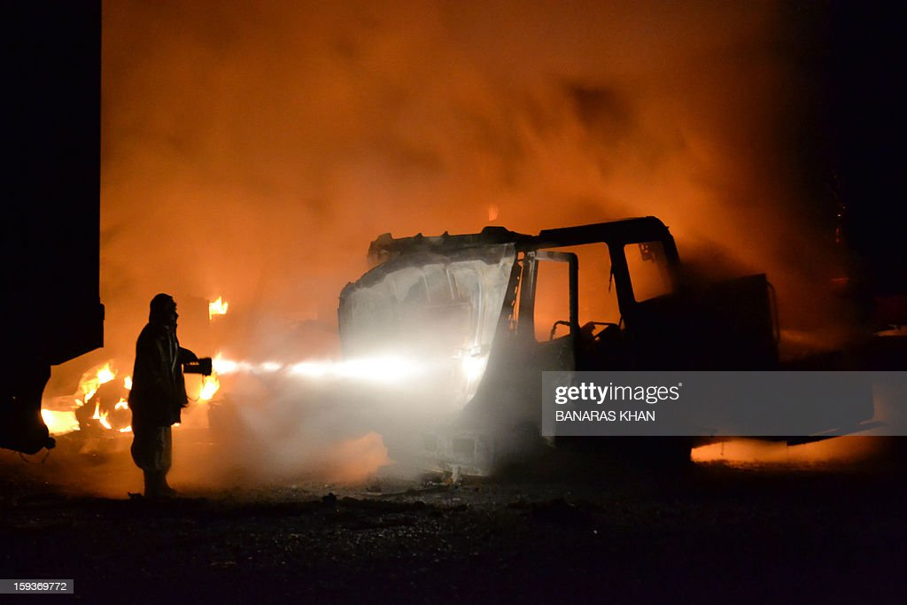 A Pakistani fireman extinguishes burning NATO supply truck in Quetta on January 11, 2013, after unidentified men fired rockets on NATO containers carrying goods for international troops operating in Afghanistan, killing one person and destroying at least five vehicles in the Hazar Ganji area on the outskirts of Quetta on Friday. Banaras KHAN