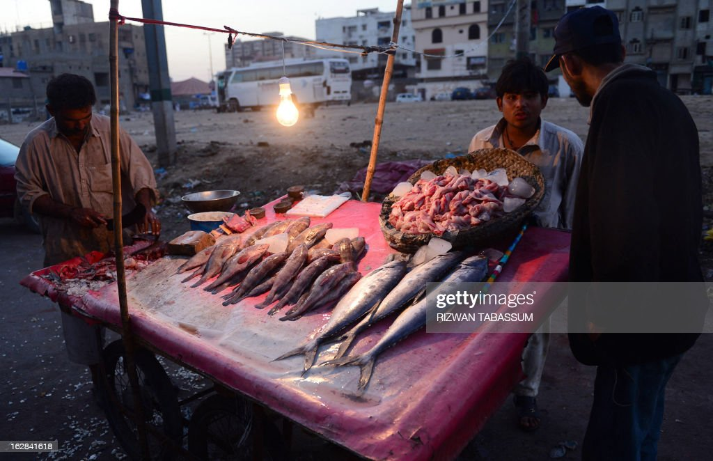 A Pakistani fish vendor speaks to a customer (R) in Karachi on February 28, 2013. The European Union is to resume imports of seafood from Pakistan, officials said, ending a six-year suspension imposed over hygiene fears. AFP PHOTO / Rizwan TABASSUM