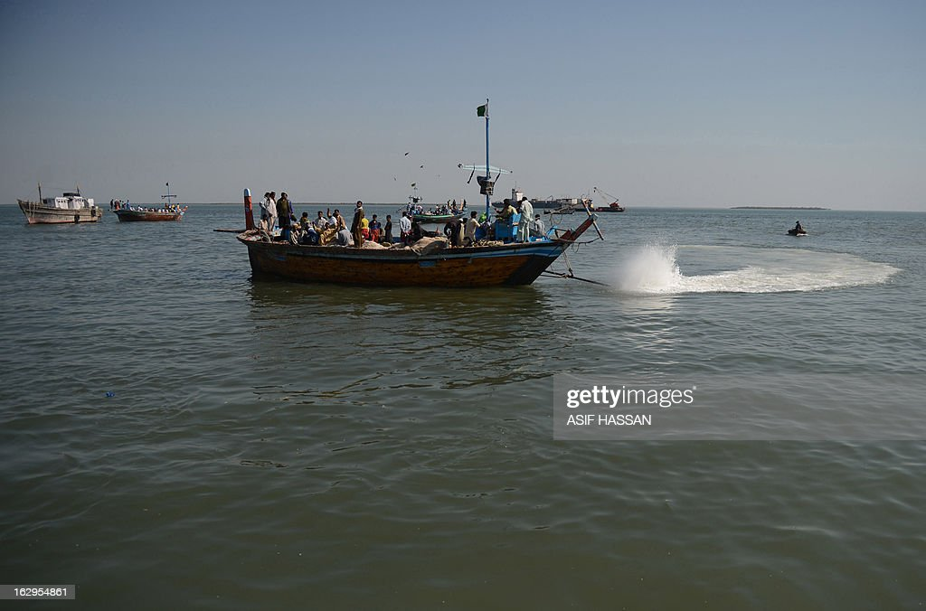 Pakistani fishermen throw their fishing nets in the Arabian sea in Karachi on March 2, 2013. The European Union is to resume imports of seafood from Pakistan, officials said, ending a six-year suspension imposed over hygiene fears. AFP PHOTO/Asif HASSAN