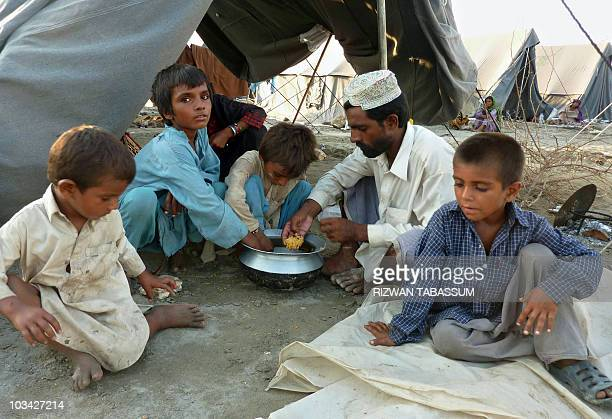 Pakistani flood survivors eat rice at a camp in Sukkur on August 17 2010 Pakistan won more aid pledges today as UN officials warned money needs to...