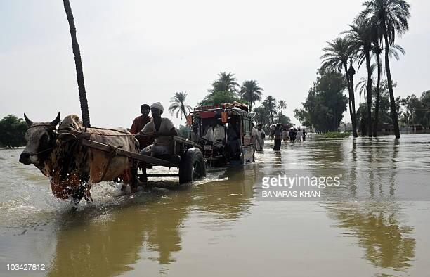 Pakistani flood survivors evacuate the flooded area near Bassera village on August 17 2010Pakistan won more aid pledges today as UN officials warned...