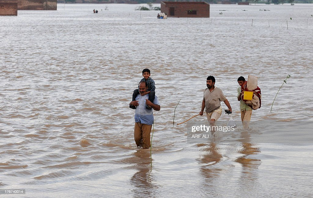 Pakistani flood-affected people wade through flood waters at Kala Shah Kako on August 18, 2013. Heavy monsoon rains have triggered floods affecting more than 300,000 people across Pakistan in the last two weeks and killed 108 others, disaster management officials said. AFP PHOTO/Arif ALI