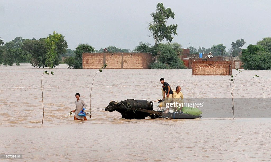 Pakistani flood-affected people wade through flood waters in Kala Shah Kako on August 18, 2013. Heavy monsoon rains have triggered floods affecting more than 300,000 people across Pakistan in the last two weeks and killed 108 others, disaster management officials said. AFP PHOTO/Arif ALI
