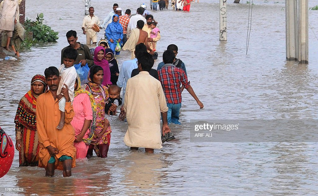 Pakistani flood-affected residents wade through flood waters at Kala Shah Kako on August 18, 2013. Heavy monsoon rains have triggered floods affecting more than 300,000 people across Pakistan in the last two weeks and killed 108 others, disaster management officials said. AFP PHOTO/Arif ALI