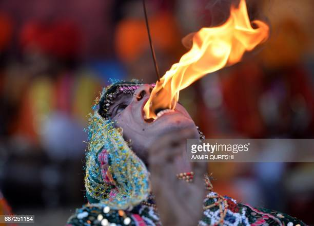 A Pakistani folk artist from Cholistan breathes fire as he performs during the annual Lok Mela festival in Islamabad on April 11 2017 The festival is...