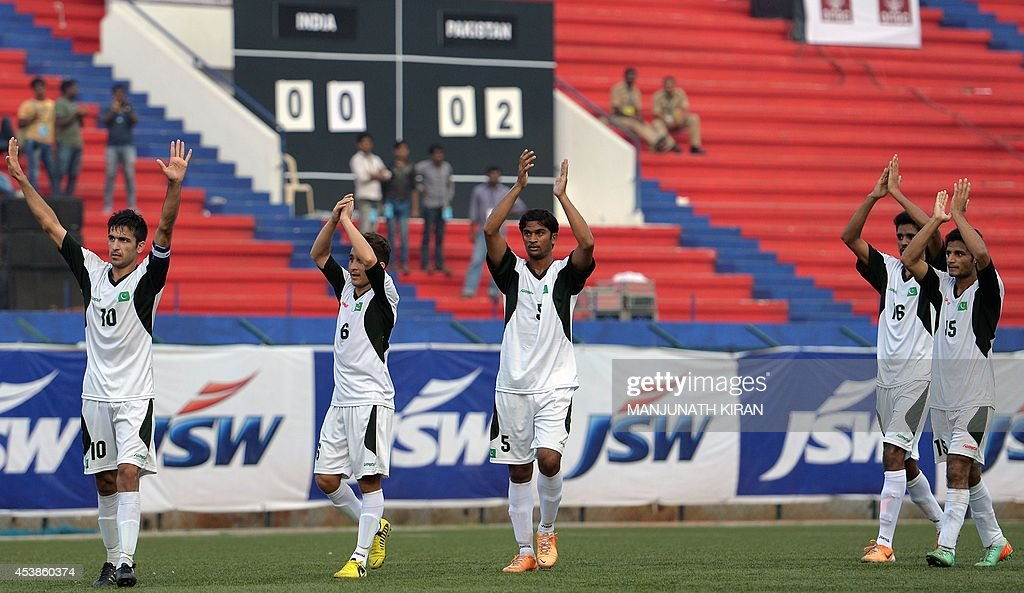 Pakistani football team captain Kaleem Ullah (L) and teammates gesture to spectators as they celebrate their two-goal victory against India during their second friendly football match in Bangalore at the Karnataka State Football Association Stadium in Bangalore on August 20, 2014. Pakistan pulled off a surprise 2-0 win over India, with a late goal from Saddam Hussain ensuring a share of the spoils for the visitors in the first football series between the arch rivals for a decade. AFP PHOTO/Manjunath KIRAN
