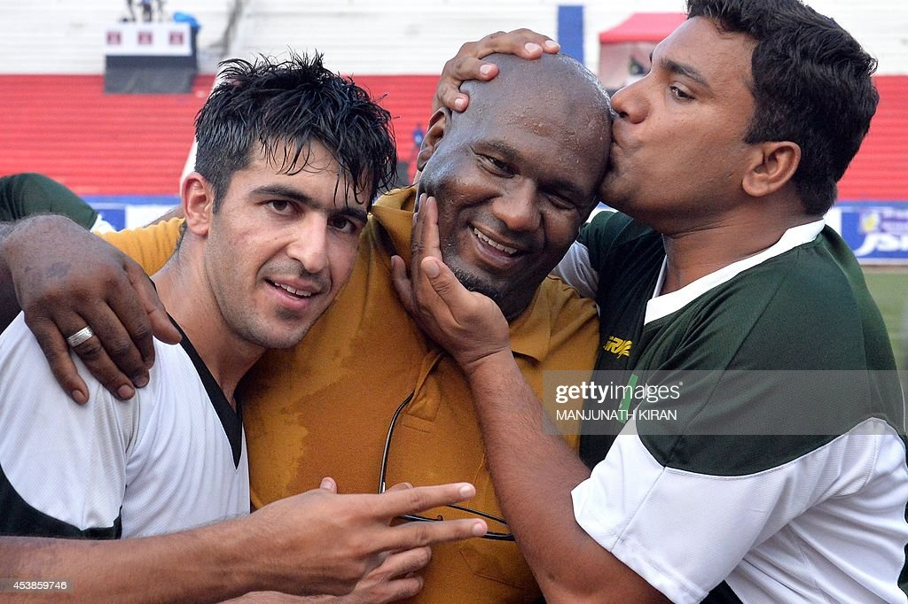 Pakistani football team captain Kaleem Ullah (L) looks on as their coach Mohammad Shamlan Mubarak Basheer Al Shamlan (C) gets a kiss from Pakistani Foootball Association official Farooq as they celebrate their two-goal victory against India during their second friendly football match in Bangalore at the Karnataka State Football Association Stadium in Bangalore on August 20, 2014. Pakistan pulled off a surprise 2-0 win over India, with a late goal from Saddam Hussain ensuring a share of the spoils for the visitors in the first football series between the arch rivals for a decade. AFP PHOTO/Manjunath KIRAN