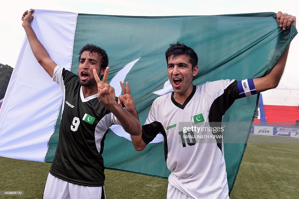 Pakistani football team captain Kaleem Ullah (R) with teammate Saddam Hussain, who both scored goals in the match, celebrate their two-goal victory against India in their second friendly football match in Bangalore at the Karnataka State Football Association Stadium in Bangalore on August 20, 2014. Pakistan pulled off a surprise 2-0 win over India, with a late goal from Saddam Hussain ensuring a share of the spoils for the visitors in the first football series between the arch rivals for a decade. AFP PHOTO/Manjunath KIRAN