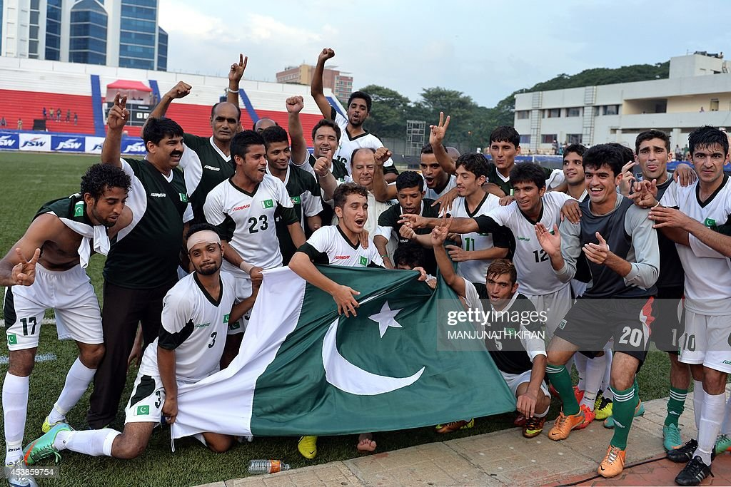Pakistani footballers and team officials celebrate their two-goal victory against India during their second friendly football match in Bangalore at the Karnataka State Football Association Stadium in Bangalore on August 20, 2014. Pakistan pulled off a surprise 2-0 win over India, with a late goal from Saddam Hussain ensuring a share of the spoils for the visitors in the first football series between the arch rivals for a decade. AFP PHOTO/Manjunath KIRAN