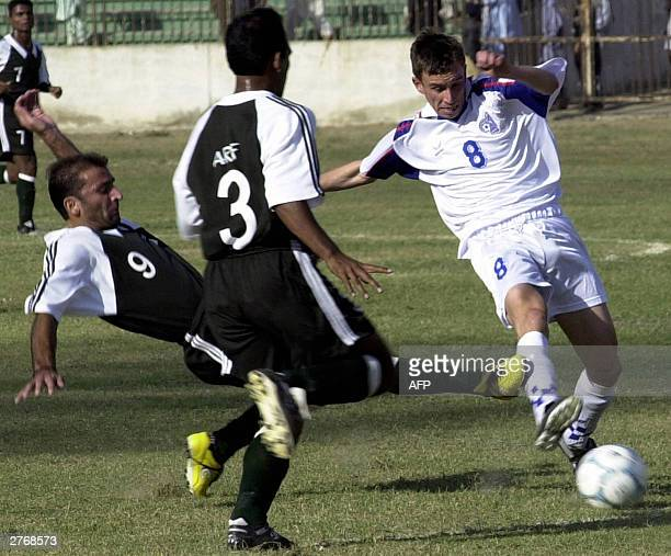 Pakistani footballers Sajjad Hayder Mohammad Tariq attempt to tackle Kyrgyzstan player Harchenko Adim as he dribbles the ball in their World Cup...