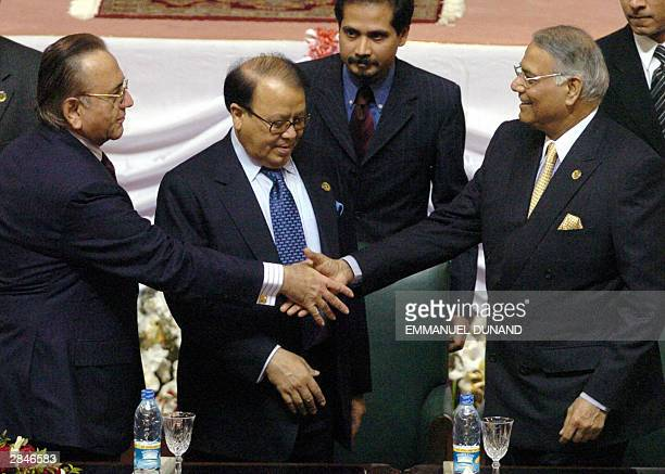 Pakistani Foreign Minister Khurshid Mahmud Kasuri and his Indian counterpart Yashwant Sinha shake hands as Bangladeshi Foreign Minister Morshed Khan...