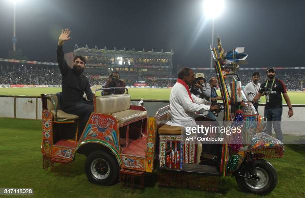 Pakistani former captain Misbah ul Haq rides on an autorickshaw as he waves to crowd during the third and final Twenty20 International match between...