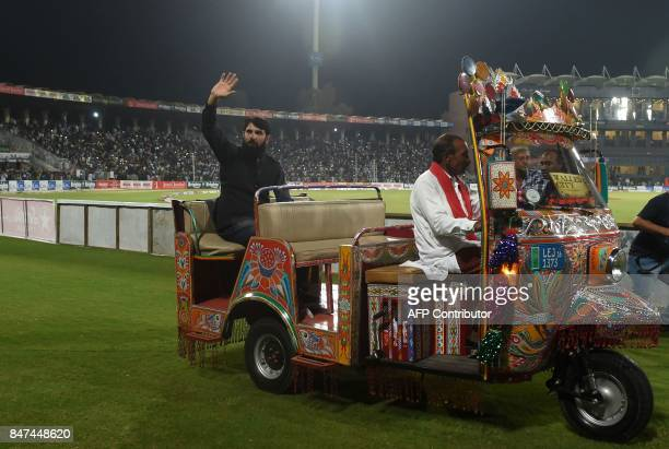 Pakistani former captain Misbah ul Haq rides on an autorickshaw as he waves to the crowd during the third and final Twenty20 International match...
