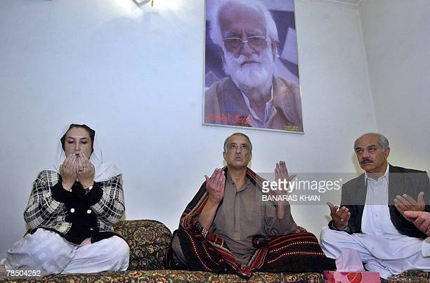Pakistani former prime minister Benazir Bhutto prays for late slain rebel tribal chief Nawab Akbar Bugti as Bugti's son Talal Bugti joins her during...