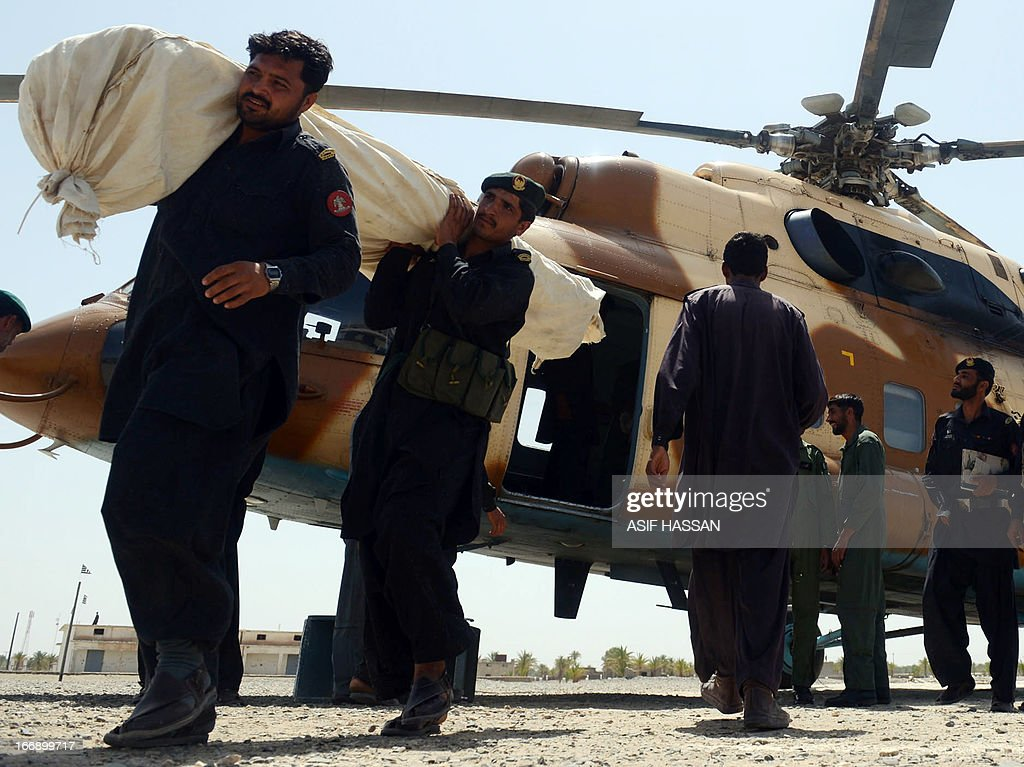 Pakistani Frontier Constables unload relief supplies from an Mi-171 army helicopter in the quake hit Mashkail area of southwestern Baluchistan province on April 18, 2013. More than 12,000 Pakistanis living in a remote, impoverished southwestern desert region near the Iranian border have been affected by this week's huge earthquake, a relief official said.