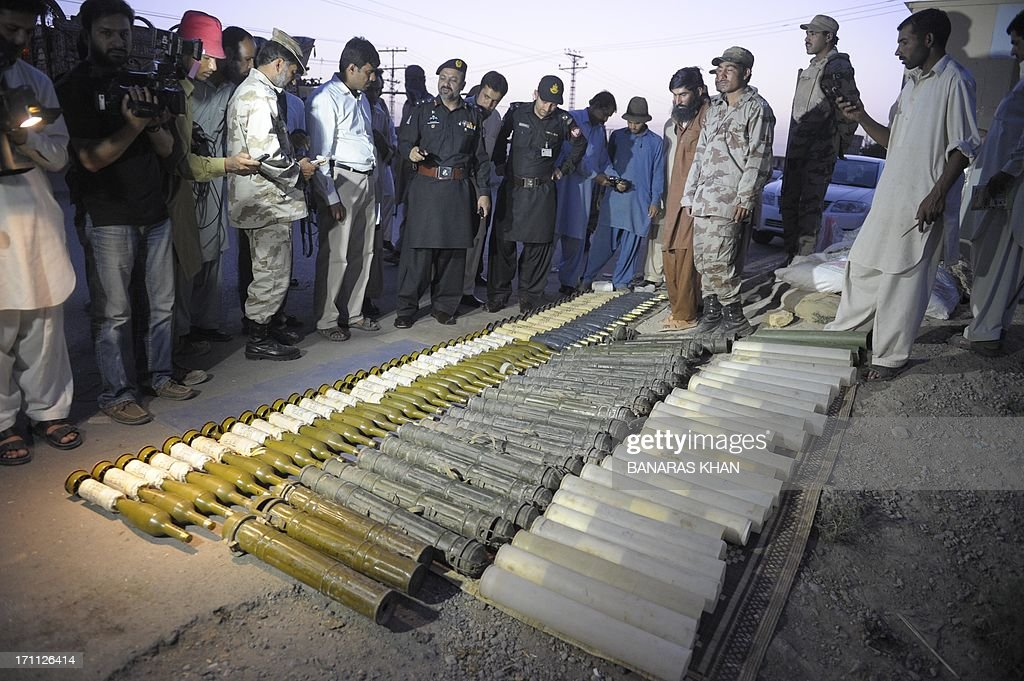 Pakistani Frontier Corps (FC) and members of the media gather around seized rockets at a check point in Quetta on June 22, 2013. Local chief of paramilitary Frontier Corps (FC) Colonel Maqbool Ahmad told AFP that 'We intercepted the truck, which was coming from the border town of Chaman on an intelligence tip off and arrested the driver after recovering 50 rockets with fuses'. AFP PHOTO/Banaras KHAN