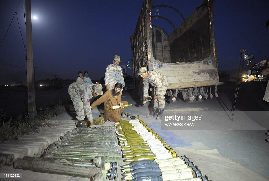 Pakistani Frontier Corps (FC) arrange the seized rockets at a check point in Quetta on June 22, 2013. Local chief of paramilitary Frontier Corps (FC) colonel Maqbool Ahmad told AFP that 'We intercepted the truck, which was coming from the border town of Chaman on an intelligence tip off and arrested the driver after recovering 50 rockets with fuses'. AFP PHOTO/Banaras KHAN