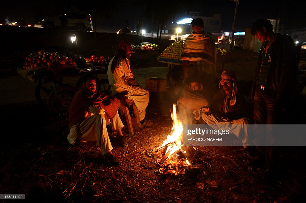 Pakistani fruit vendors warm themselves around fire on a street in Islamabad on December 11, 2012. Pakistan Meteorological Department forecast mainly cold and dry weather in most parts of the country during next 24 hours. AFP PHOTO/Farooq NAEEM