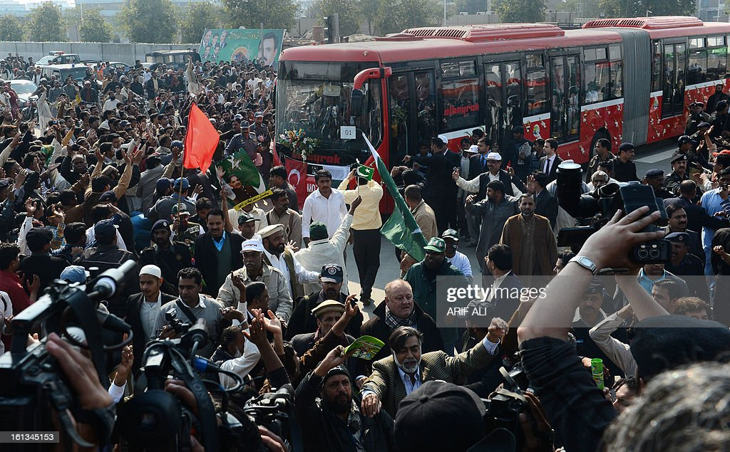 Pakistani gather around a Metrobus during the launch of the Metro Bus system in Lahore on February 10, 2013. Authorities in Pakistan on Sunday launched a 'Metro Bus' system in the second largest city, Lahore, the restive country's first major urban public transport scheme. AFP PHOTO/Arif ALI