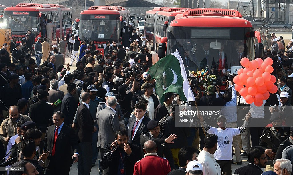 Pakistani gather around the Metrobuses during the launch ceremony of the Metro Bus system in Lahore on February 10, 2013. Authorities in Pakistan on Sunday launched a 'Metro Bus' system in the second largest city, Lahore, the restive country's first major urban public transport scheme. AFP PHOTO/Arif ALI