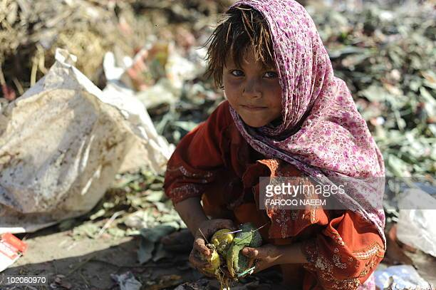 A Pakistani girl collects scavengable food from a garbage dump in Islamabad on June 12 World Day against Child Labour The UN Children's Fund called...