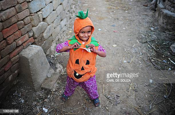 A Pakistani girl wearing a halloween costume holds a ten rupee note in a slum area in Islamabad on October 29 2010 Halloween is a festival celebrated...