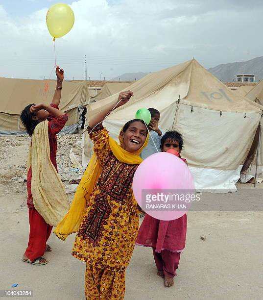 Pakistani girls displaced by floods play at a makeshift camp to celebrate Eid alFitr during the first day of the religious festival in Quetta on...