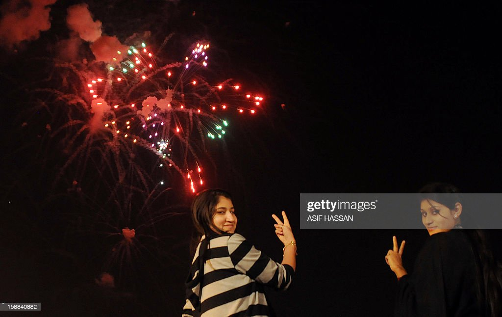 Pakistani girls pose for a photograph during a fireworks display at Clifton Beach in Karachi to celebrate the New Year early on January 1, 2013. World cities from Sydney and Hong Kong to Dubai and London rang in the New Year with spectacular fireworks, as revelers at Times Square in New York sought to top off the global extravaganza. AFP PHOTO / Asif HASSAN