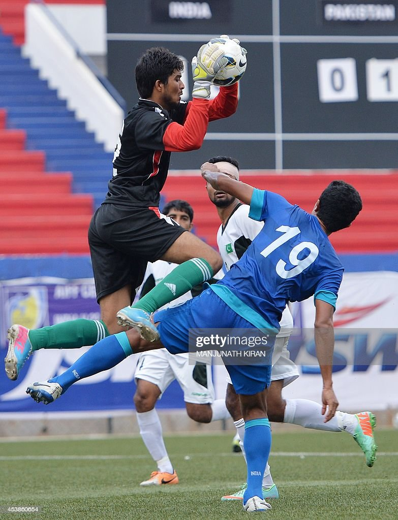 Pakistani goalkeeper Muzammil Hussain (L) makes a save against an attempt by India during their second friendly football match in Bangalore at the Karnataka State Football Association Stadium in Bangalore on August 20, 2014. Pakistan pulled off a surprise 2-0 win over India, with a late goal from Saddam Hussain ensuring a share of the spoils for the visitors in the first football series between the arch rivals for a decade. AFP PHOTO/Manjunath KIRAN