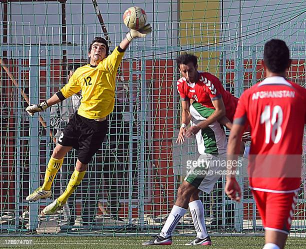 Pakistani goalkeeper Saqib Hanif makes a save during a football match between Afghanistan and Pakistan at the Afghanistan Football Federation stadium...