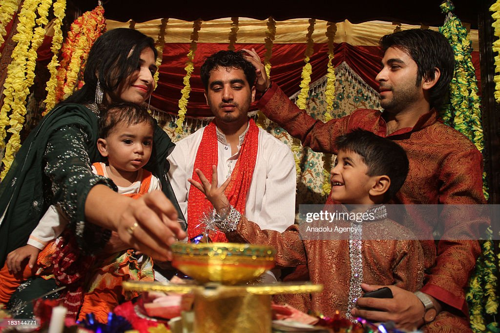 Pakistani groom's relatives feed him with the traditional sweets during a henna ceremony on October 4, 2013 in Rawalpindi, Pakistan. Traditional meal such as halwa poori, aloo bhujia, rice and haleem is being served at the ceremony. As the weather is getting colder, people show high demand for the marriage in Pakistan. The Young segment of Pakistan's population is growing rapidly and its covers around 35 percent of the population.