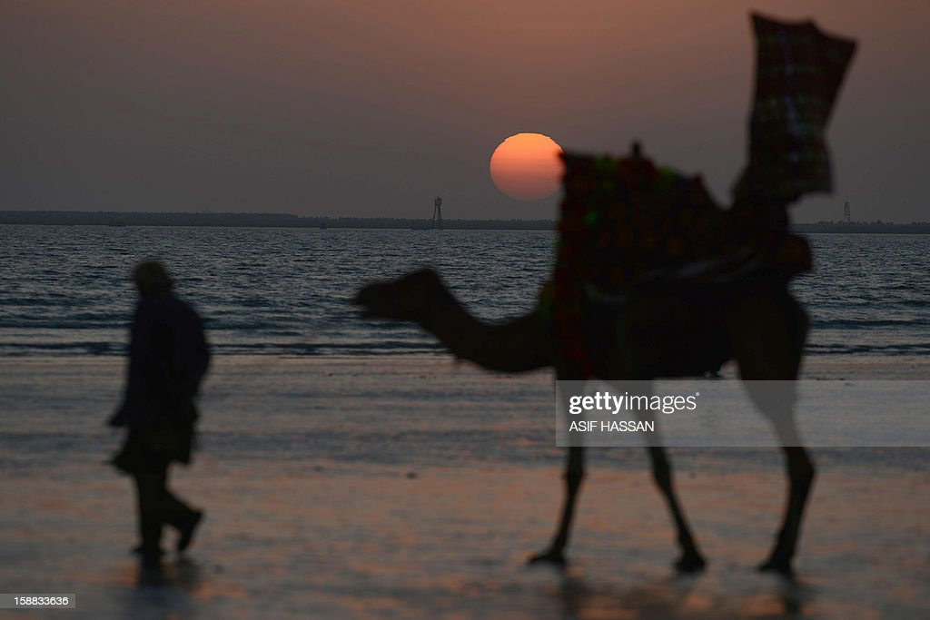 A Pakistani guide pulls his camel during the last sunset of 2012 at Clifton beach in Karachi on December 31, 2012. Sydney will kick off a wave of dazzling firework displays welcoming in 2013, from Dubai to Moscow and London, with long-isolated Yangon joining the global pyrotechnics for the first time.